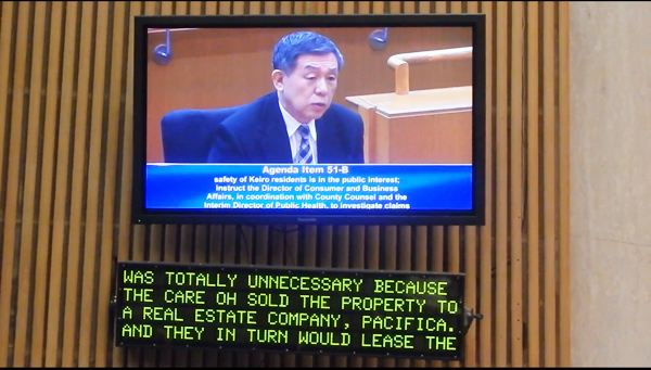 On behalf of concerned Japanese American community about the Kiero issue, Little Tokyo phisician Takeshi Matsumoto testifies before the Los Angeles County Board on April 12. Shown is Dr. Matsumoto interview on a monitor screen of the Board's Hearing Room. (Cultural News Video)
