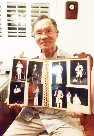 Mr. Tak Nishi shows his photo album of Japanese song stages that he emceed and coordinated. (Cultural News Photo)