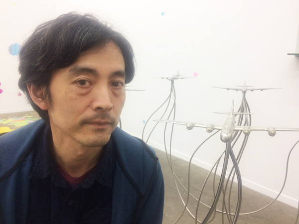 "Naohiko Onodera and his work ""The Super Fortress"" 2016, pewter and stainless steel, 37 x 120  x 54 inches. (Cultural News Photo)"