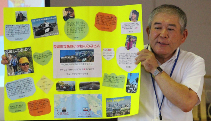Mr. Toshihiro Shibata, principal of Iino Elementary School, shows a message board from a Los Angeles group that sent a donation to the school in early June 2016 soon after the earthquake in Kumamoto Prefecture, Japan. (Courtesy of Walk and Talk)